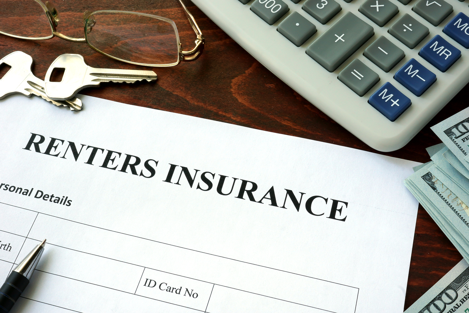Renters insurance form and dollars on the table.